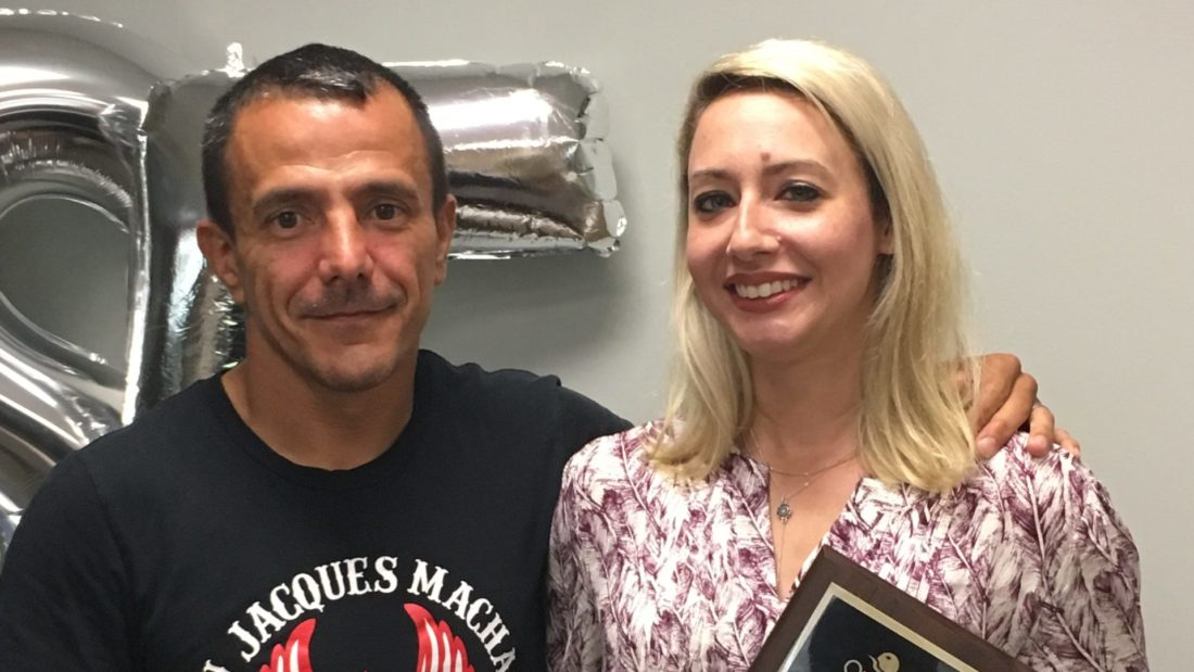 Man and woman posing with plaque award