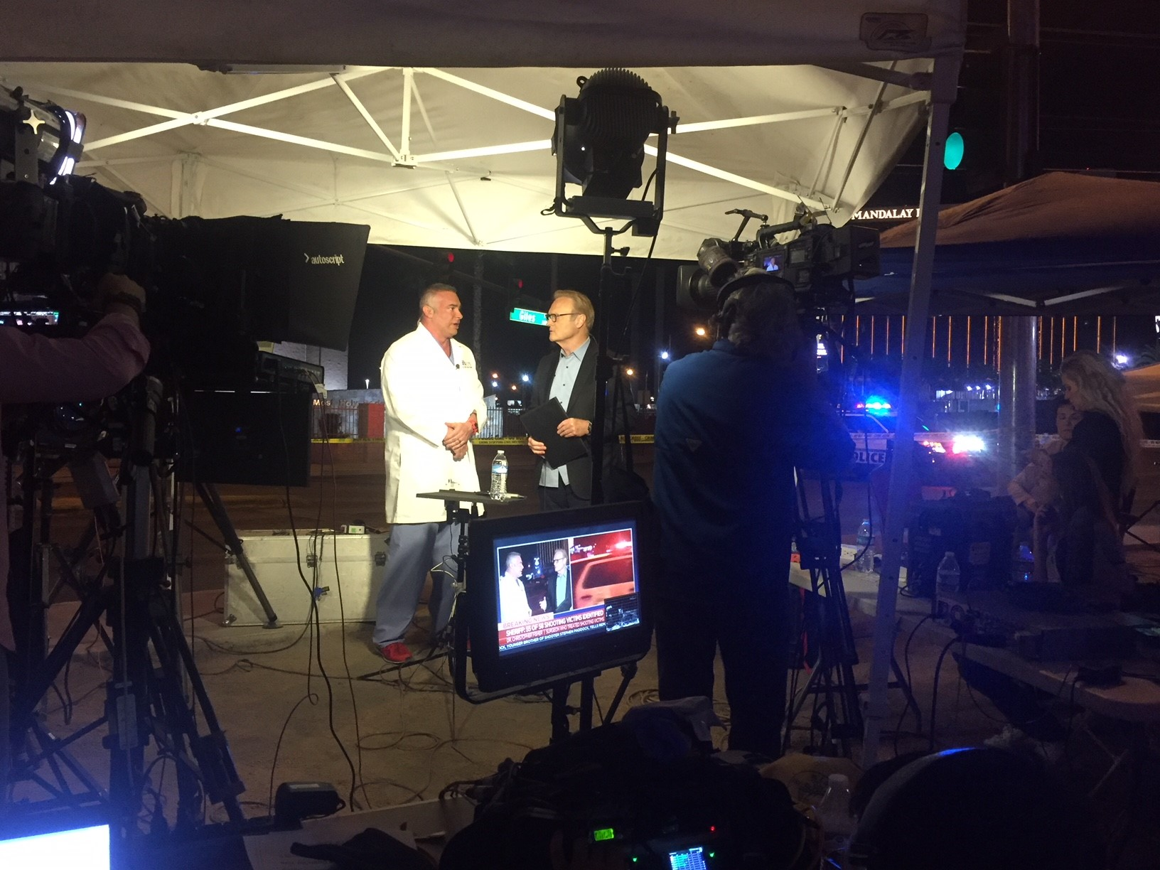 Male doctor being interviewed by male TV show host in front of camera crew