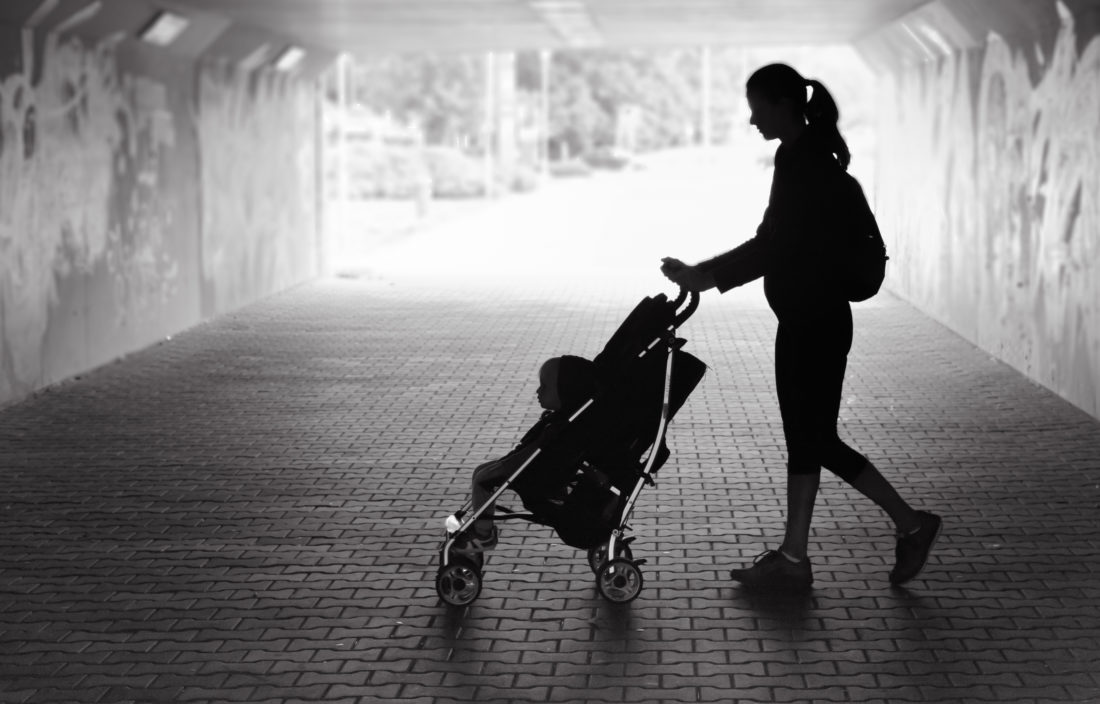 Silhouette of a woman pushing a stroller in a city tunnel