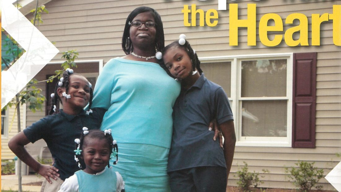 """Lillie McClain (pictured in 2005) with her daughters Kayla, Jada and Courtney standing in front of a house with a """"Hope from the Heart"""" sign."""