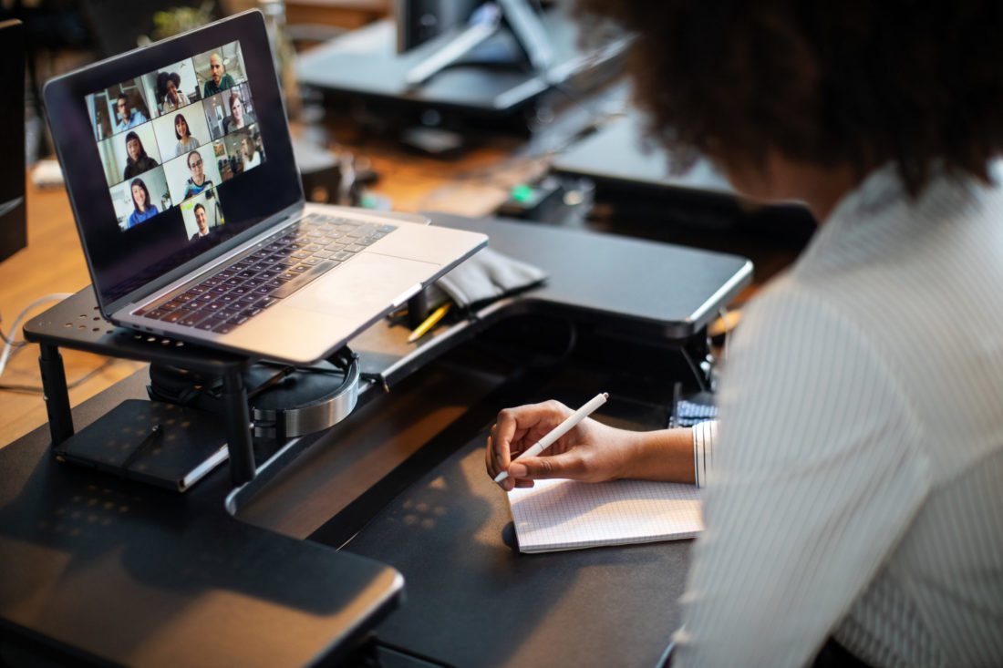 Woman sitting at desk with laptop during team video call