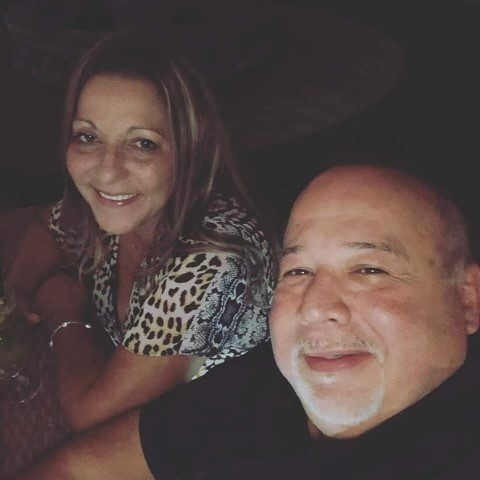 Man and woman sitting next to each other and smiling for a photo