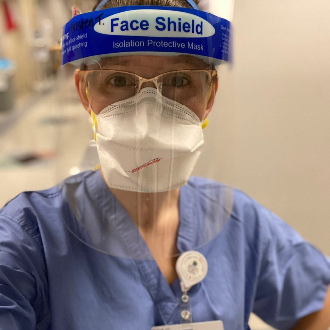 A female nurse wearing a face mask and face shield