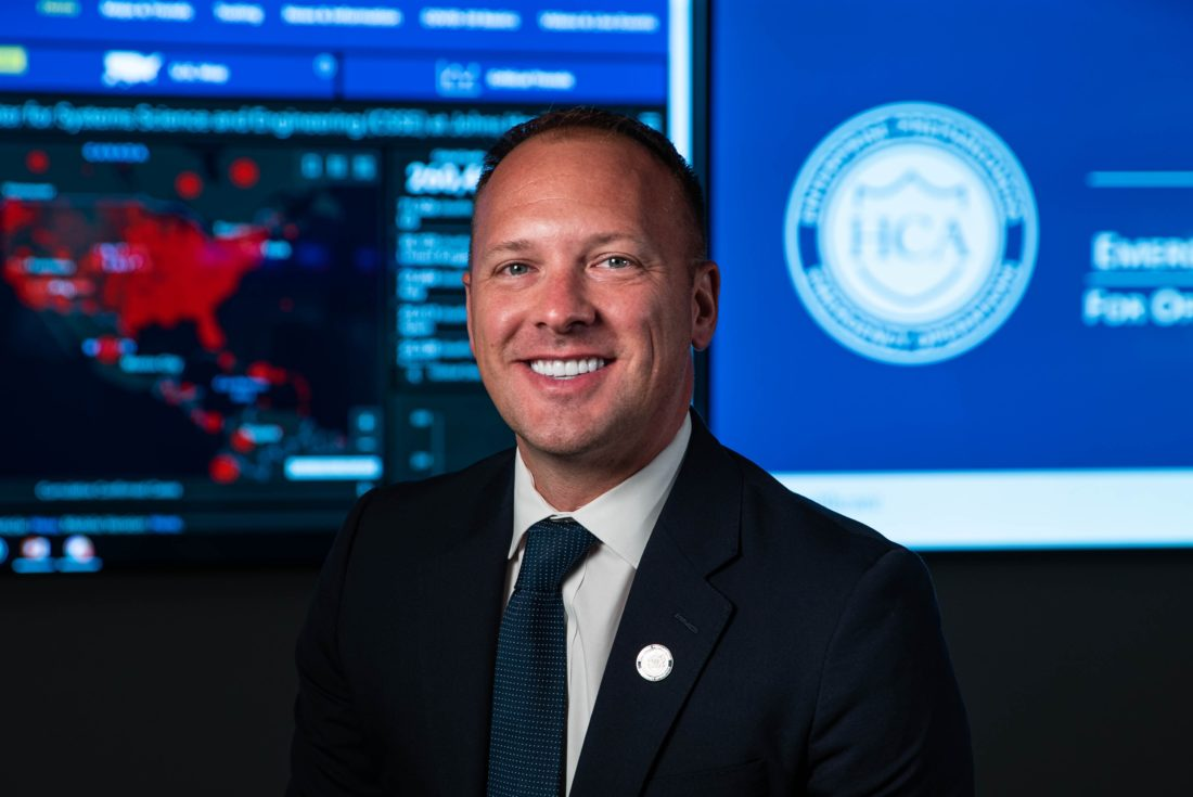 Man wearing a suit and tie. Behind him is a screen with a map of the United States.
